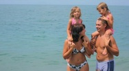 Man and woman standing on beach holding little girls on shoulders Stock Footage