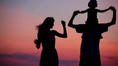 Woman and man holding little girl on shoulders dancing on sunset Stock Footage