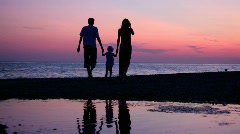 Woman, man and little girl having joined hands walking on sunset sea coast Stock Footage