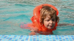 Happy little girl dressed in inflatable jacket swims in pool Stock Footage