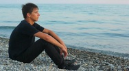 Teenager sits on pebble beach and looks at sea, profile Stock Footage