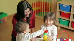 Two little girls and female teacher in kindergarten Stock Footage