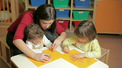 Little girls and teacher playing with colors in kindergarten Stock Footage