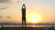 Stock Video Footage of Man doing exercises on a beach at sunrise