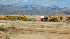 Heavy dirt machines - 2 - parked machinery with mountain background Stock Footage