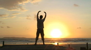 Stock Video Footage of Man meditating on a beach at sunrise