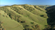 Stock Video Footage of Aerial view of unspoiled green undulating hillside