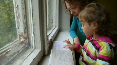 Woman and girl turns over the pages of medical report Stock Footage
