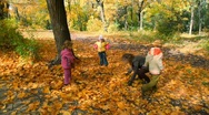 Family throwing leaves in park Stock Footage