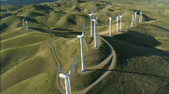 Aerial view of wind turbines in green hillside - stock footage