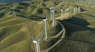 Stock Video Footage of Aerial view of wind turbines in green hillside