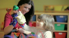 Female teacher and little girl playing in kindergarten Stock Footage