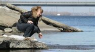 Woman plays water on river bank. Stock Footage