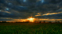 Sunset over grass field hdr time lapse Stock Footage