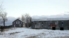 A cold winterwind blows gusts of snow off a barn-roof - stock footage