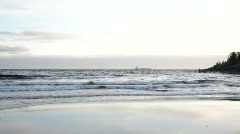 Waves are rolling unto a sandy beach. - stock footage