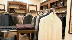 Rows of hangers with jacket and shelves with clothes and jeans Stock Footage