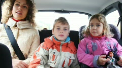 Mum, daughter and son sit on back seat of car Stock Footage