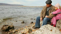 daddy with daughter sit on stone on river bank - stock footage