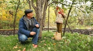 Stock Video Footage of boy pick apple from apple-tree, grandfather sits nearby