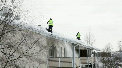 Cleaning snow from the roof in spring 1 Stock Footage