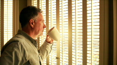 Man drinking coffee at window Stock Footage