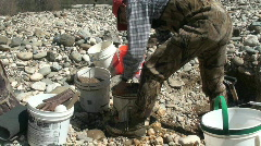 Miner digging for gold bearing gravel Stock Footage
