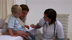 Assertive doctor examining a little boy's arm - stock footage