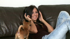 Cheerful woman listening music and playing with her dog - stock footage
