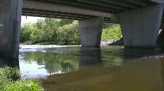 Flowing river under a concrete bridge - stock footage