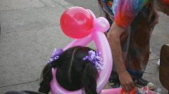Street fair event - 1 - 9 - baloon head gear on a little girl - stock footage