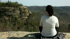 Girl sitting cross legged on rock - stock footage