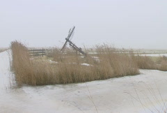 Frozen Dutch winter landscape with windmills and ice on the water Stock Footage