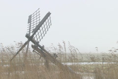 Frozen Dutch winter landscape with windmills and ice on the water NTSC Stock Footage