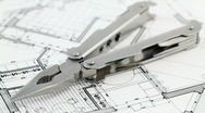 Pliers and architectural blueprints Stock Footage