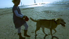 Child and mother walking with dog on the beach Stock Footage