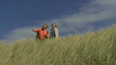 WS, Portrait of father and daughter on dunes overlooking the sea Stock Footage