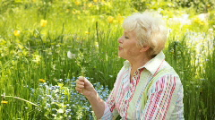 Senior woman with dandelion Stock Footage