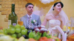 bridegroom and bride sits at wedding table - stock footage