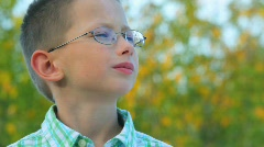 Bespectacled boy stands against trees Stock Footage