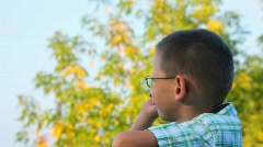 Bespectacled boy jerkes his finger forward in park Stock Footage