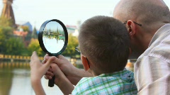 Father and son standing on bank of river and looks through magnifying glass Stock Footage