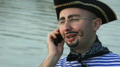 Man in pirate costume is speaking on the phone Stock Footage