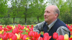 Bald-headed man with moustache sits among flowers Stock Footage