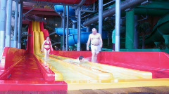 People slide from slide in an aquapark, blured faces Stock Footage