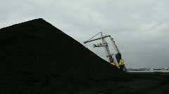 Turning crane next to pile of coals Stock Footage