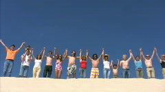 Fifteen persons jumping on sandy hill Stock Footage