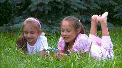 Girls lying on grass in park and talks Stock Footage