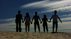 Five persons having joined hands jumps on sand Stock Footage