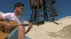 Singing man with harmonica plays guitar on beach Stock Footage